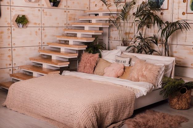 ベッドと階段のある美しい家の居心地の良いインテリア