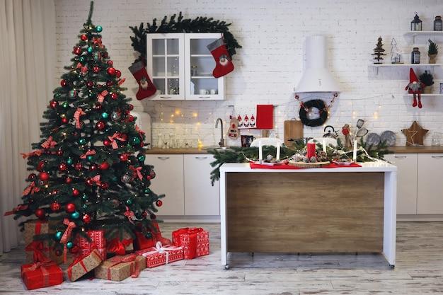 크리스마스 축하를 위해 장식된 주방의 아름다운 홈 인테리어. 따뜻한 분위기. 전경에 빨간색 장식된 크리스마스 트리입니다. 사람이 없다