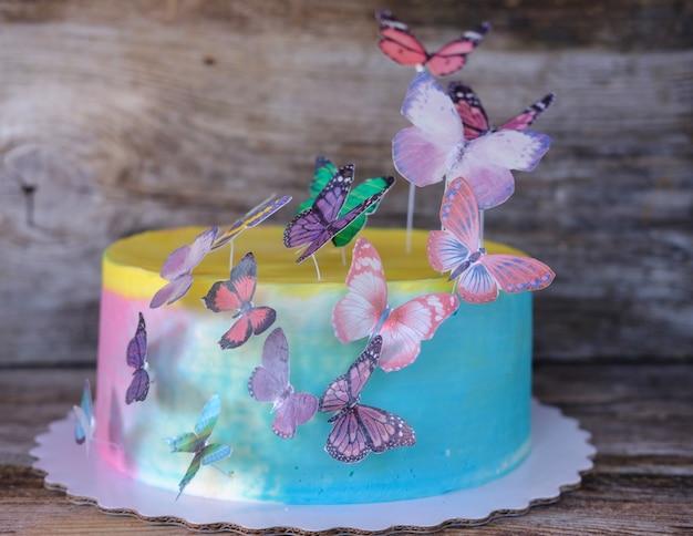 여러 가지 빛깔의 크림과 나비와 함께 아름다운 집에서 만든 아기 케이크