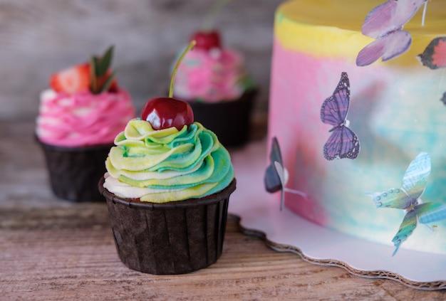 컬러 버터 크림, 웨이퍼 나비 및 컵 케이크와 함께 아름다운 수제 베이비 케이크