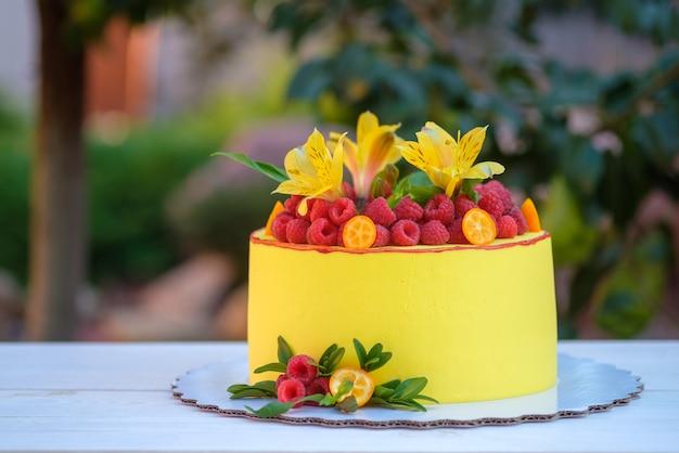 生きたユリと新鮮なラズベリーで飾られた、明るい黄色のアイシングの美しい自家製ケーキ
