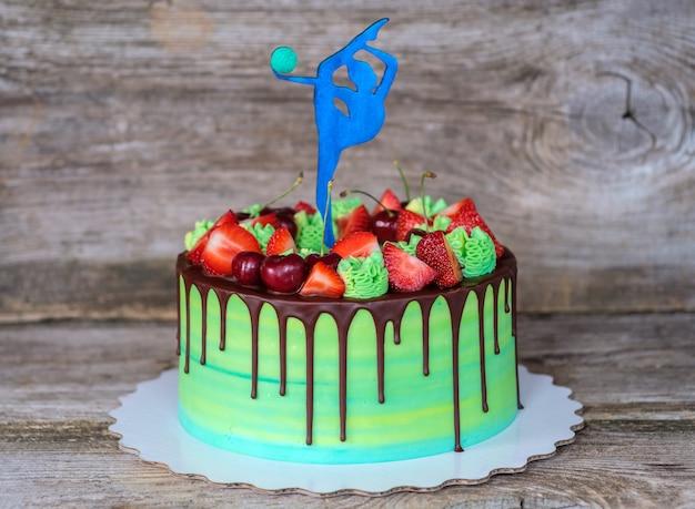 木製のテーブルの上に、ボールを持った体操選手の姿で飾られた、緑のチーズクリームと美しい自家製ケーキ