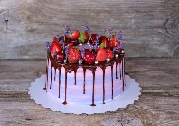 ラベンダーの花、イチゴ、さくらんぼで飾られた紫色のチーズクリームと美しい自家製ケーキ