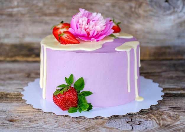 라이브 핑크 모란과 딸기 열매로 장식 된 보라색 치즈 크림과 함께 아름다운 수제 케이크