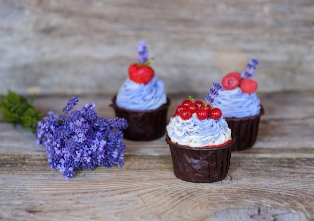 Красивые домашние капкейки с фиолетовым сырным кремом, украшенные ягодами смородины, малины и клубники, и букетом лаванды.
