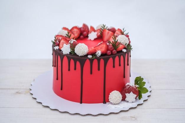Beautiful homemade red cake with fresh strawberry berries on white background. wedding cake, birthday cake, holiday dessert