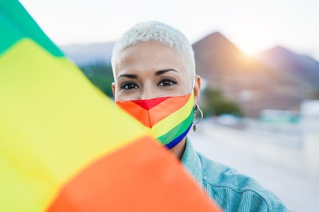 Lgbtプライドレインボーフラッグ屋外の美しい同性愛ラテン女性