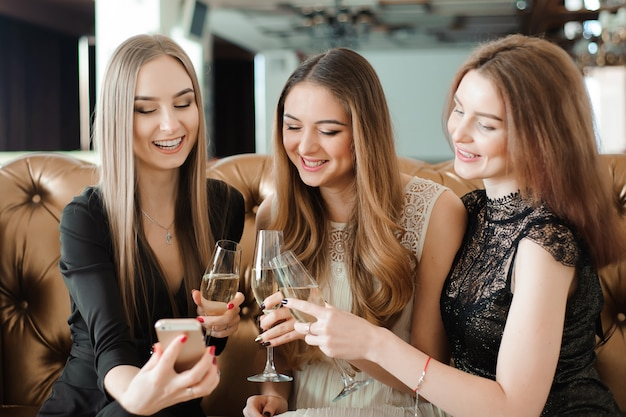 Beautiful hot girls having party fun, drinking champagne