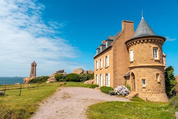 フランス、ブルターニュのコートダモール、ペロスギレックの町にあるプルマナッコ港のミーンルス灯台の隣にある美しい家。