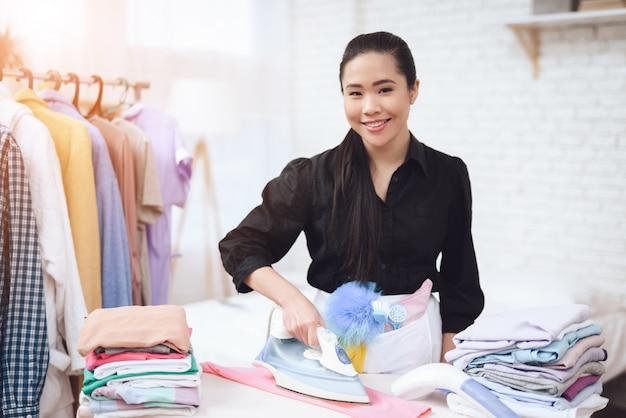 Beautiful housekeeper in black uniform ironing