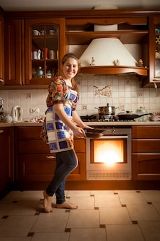 Beautiful housewife baking cookies in oven on country style kitchen