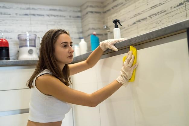 Красивая хозяйка убирает полки на кухне. концепция домашней чистоты