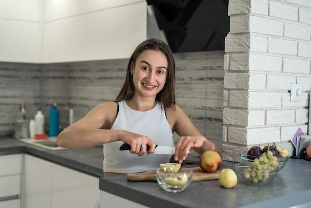 キッチンでの朝食の調理過程で美しい主婦。健康食品としての果物の冷凍