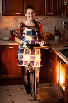Beautiful housewife holding form with chocolate cookies near oven