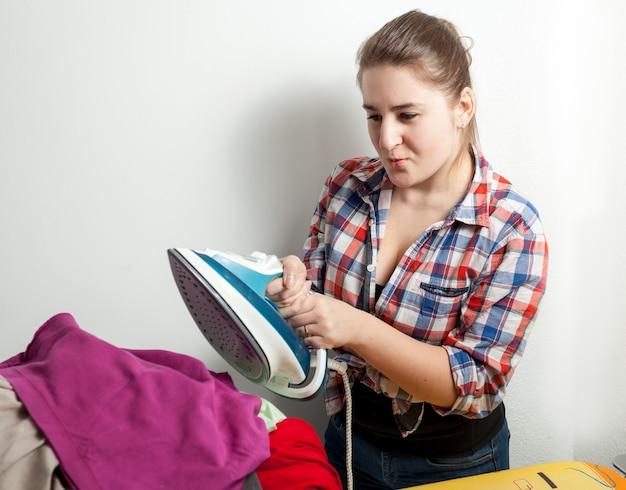 Красивая домохозяйка в рубашке гладит одежду