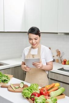 Красивая хозяйка леди держит цифровой планшет ищет рецепт интернет-лекция мастер-класс готовить вкусный семейный ужин