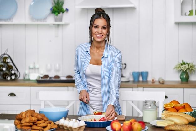 美しい主婦はケーキのためにリンゴをスライスします。女性は家族のためにパイを焼きます