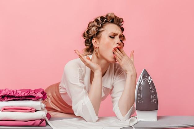 Красивая домохозяйка устало зевает и позирует с железом на розовой стене