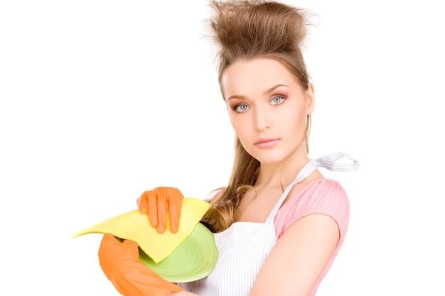 Beautiful housewife washing dish over white wall