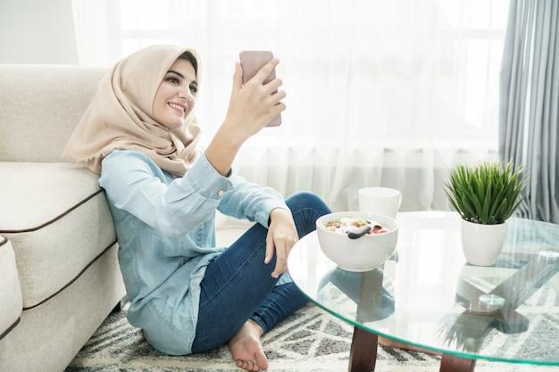 Beautiful housewife wearing hijab taking selfies in a leisure ti