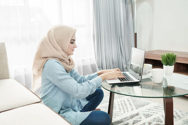 Beautiful housewife wearing hijab working on her laptop at home
