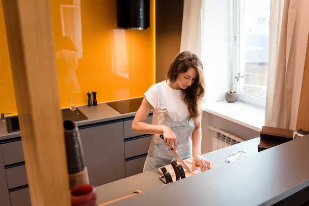 Beautiful housewife with brown hair dressed in casual clothing using knife for cutting bacon on wooden board