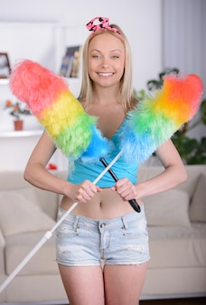 Beautiful housewife with cleaning sweep at home.