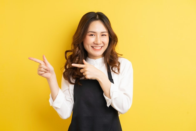 Beautiful housewife with gesture isolated on yellow