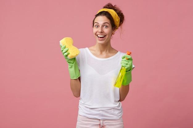 Красивая домохозяйка с желтой повязкой на голову и белой футболкой, держащая швабру и стиральный спрей, радостно выглядит, имеет хорошее настроение и хочет провести генеральную уборку в своем доме