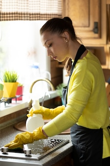 Beautiful housewife in yellow rubber gloves cleaning house wipes kitchen worktop using spray detergent, washes induction stove with sponge