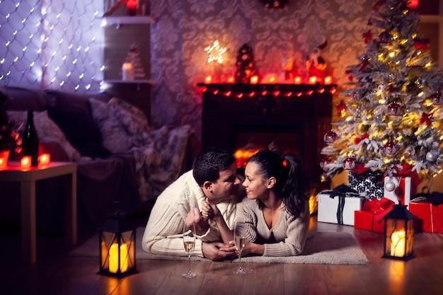 クリスマスを祝う薄暗い光の中で美しい夫と妻。クリスマスツリー。