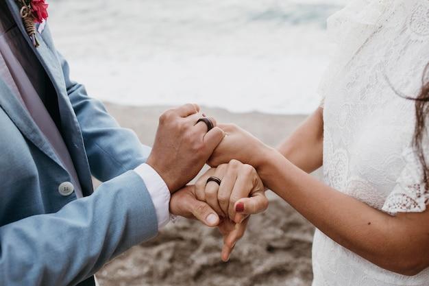 彼らの結婚式でビーチでポーズをとる美しい夫と妻