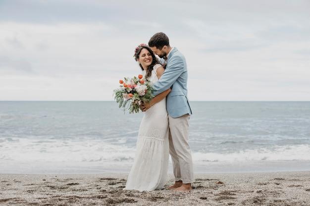 ビーチでポーズをとる美しい夫と妻