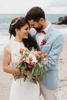 Красивые муж и жена позируют на пляже