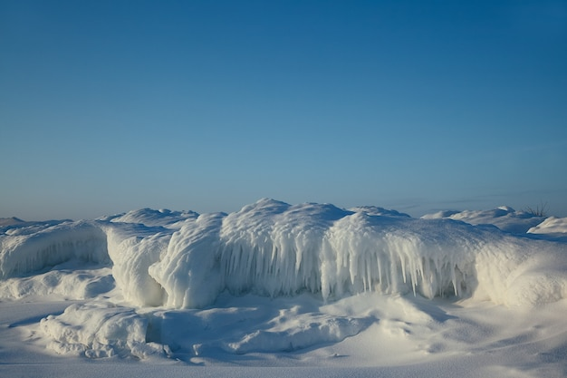 Beautiful ice formations with snow along coastline on blue sky, winter landscape