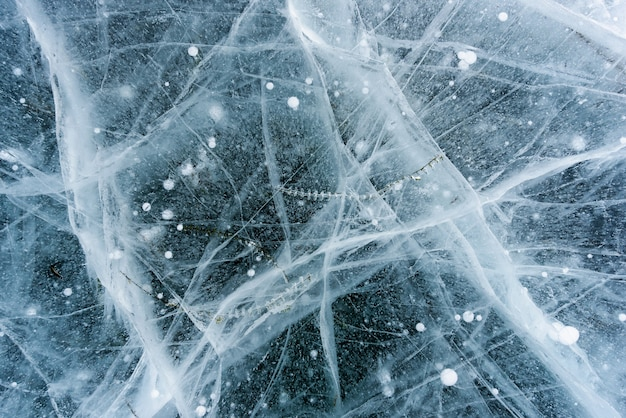 Beautiful ice of lake baikal with abstract cracks and green plant in the deep