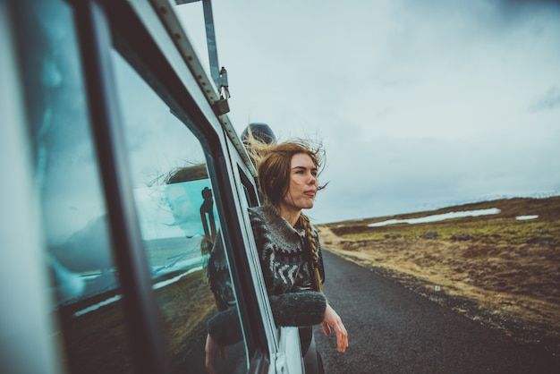 아름 다운 아이슬란드 소녀 아이슬란드에서 풍경을 즐기고 차 창 밖을 보면서