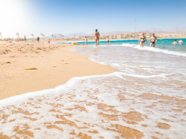 Beautiful image of calm sea waves rolling on the sandy sea beach at bright sunny day. perfect background for illustrating summer holidays, trips or vacations. place for your text. copy space