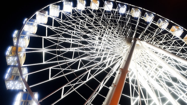Beautiful image of ferris wheel on city stret illuminated with white bulbs with night sky on the background