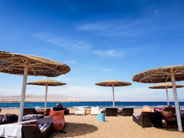 Красивое изображение пляжа с шезлонгами, лежаками и креслами-мешками под соломенными зонтиками на морском пляже против голубого неба