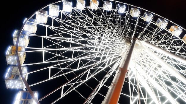 Красивое изображение колеса обозрения на городе, освещенном белыми лампочками с ночным небом на заднем плане Premium Фотографии