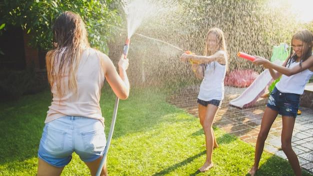 水鉄砲とガーデンホースで暑い夏の日に楽しんでいる子供たちと幸せな笑い家族の美しい画像。夏に屋外で遊んで楽しんでいる家族