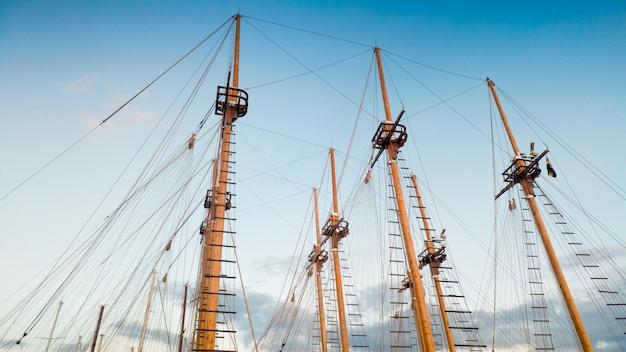 Красивое изображение высокой мачты исторических деревянных кораблей и лодок на фоне голубого неба