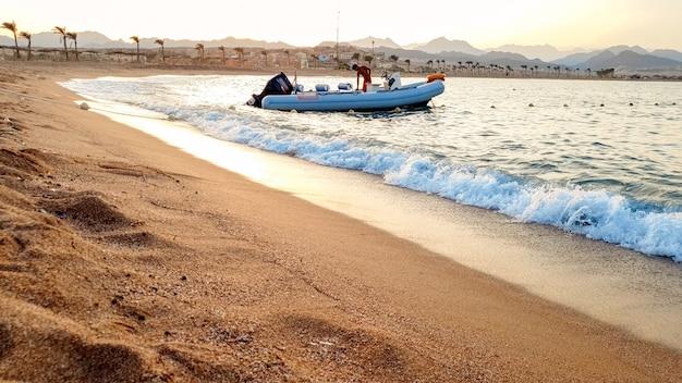 美しい夕日を背景に海の波に浮かぶインフレータブル モーター ボートの美しい画像