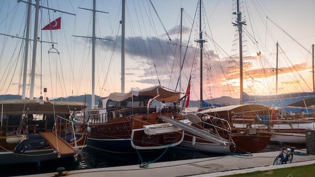 日没時に港に係留されたたくさんのヨットや木製ボートの美しい画像