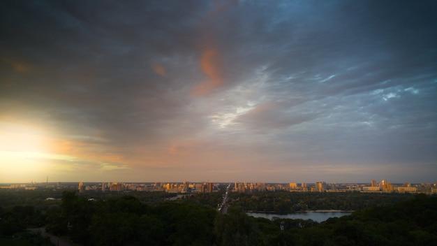 Красивое изображение закатного неба над большим городом вечером. городской пейзаж на рассвете