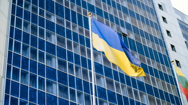 Красивое изображение украинского флага, развевающегося на ветру на фоне высокого современного офисного здания