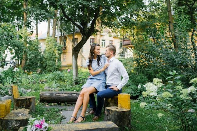 愛の幸せなカップルの男と夏の日にベンチに座っている女の子で美しい。