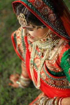 인도 결혼식에서 사리와 금색 보석을 입은 아름다운 인도 신부 무료 사진