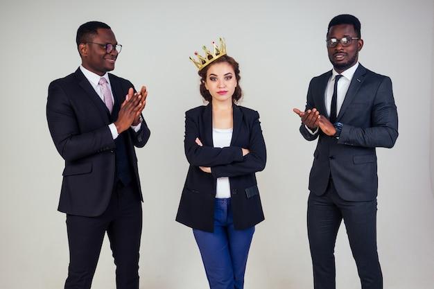 Красивая индийская бизнес-леди и два афро-американских бизнесмена аплодируют в студии на белом фоне. многонациональные смешанные расы командная работа деловых партнеров